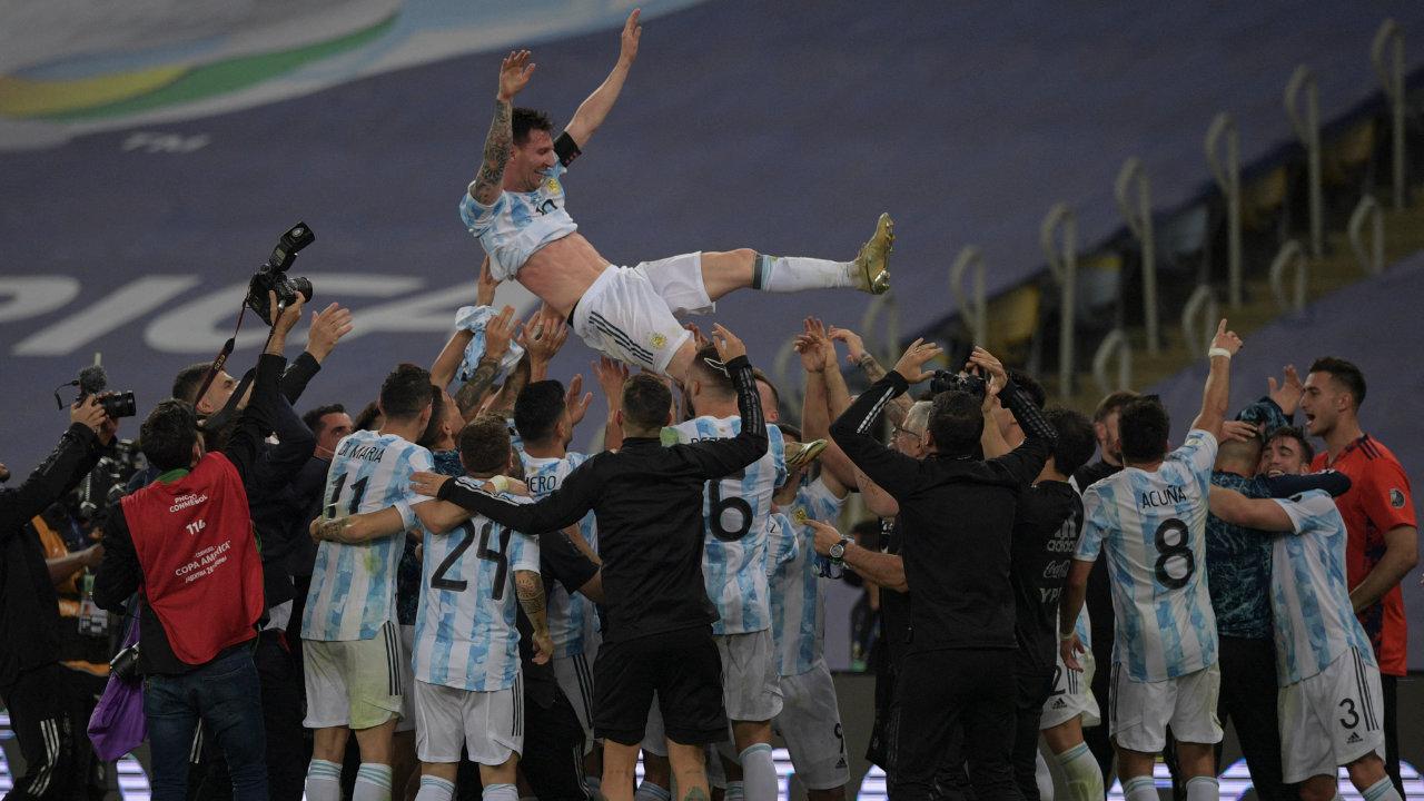 Lionel Messi en el centro de los brazos de sus compañeros